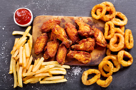 onion rings: fast food products : onion rings, french fries and fried chicken on dark table, top view