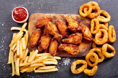Productos de comida rápida: aros de cebolla, papas fritas y pollo frito en la mesa oscura, vista superior