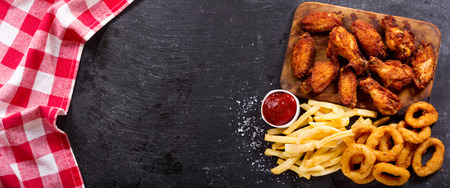 fried food: fast food products : onion rings, french fries and fried chicken on dark table, top view
