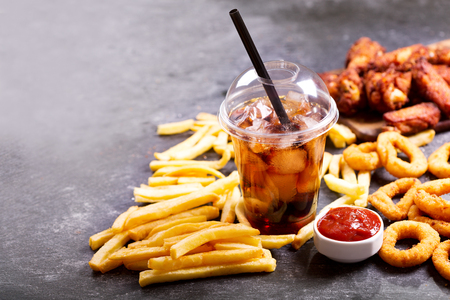 fast food meals : onion rings, french fries, glass of cola and fried chicken on dark table