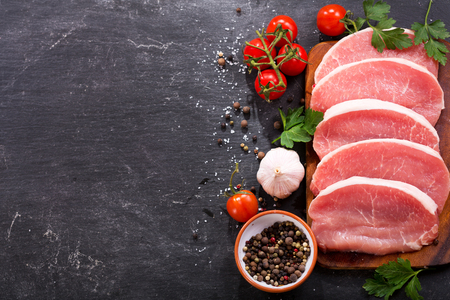 fresh pork with ingredients for cooking on dark background