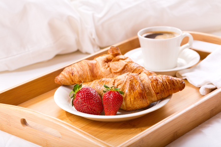 breakfast tray in bed : coffee, croissants and fresh strawberries