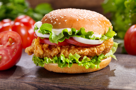 chicken burger with vegetables on a wooden table Stock Photo