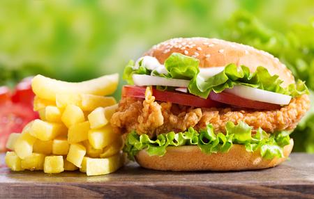 kip hamburger met frietjes op een houten tafel