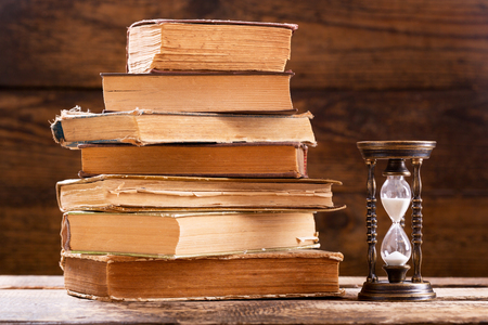 stack of old books and retro hourglass on wooden background