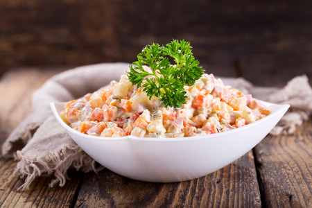 bowl of russian salad on wooden table Stock Photo