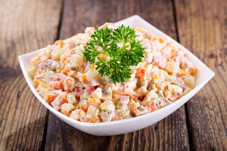 kom van Russische salade op houten tafel