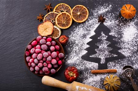 nudelholz: Zutaten zum Kochen Weihnachten Backen: Tannenbaum aus Mehl auf einem dunklen Tisch, gefrorene Cranberry und getrocknete Früchte auf dunklem Hintergrund, Draufsicht