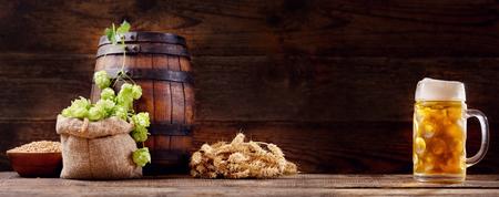 Mok bier met groene hop, tarwe oren, granen en houten vat op houten achtergrond Stockfoto