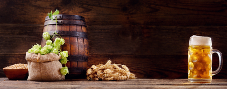 Mug of beer with green hops, wheat ears, grains and wooden barrel on wooden background Banco de Imagens