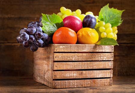 vers fruit in een houten doos op houten achtergrond Stockfoto