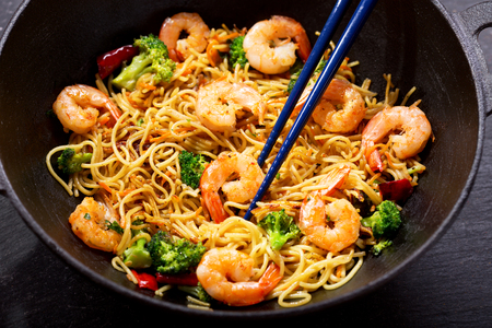 Stir fried noodles with shrimps and vegetables in a wok on dark table Stock Photo