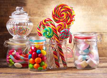 Colorful candies, lollipops and marshmallows  in a glass jars on wooden table