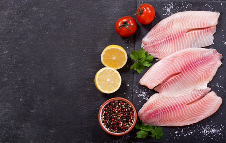 fresh fish fillet with ingredients for cooking, top view