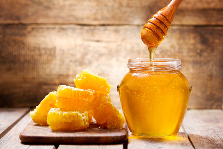 honeycombs and jar of honey on wooden background