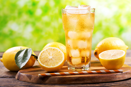glass of lemon iced tea with fresh fruits on wooden table Stock Photo
