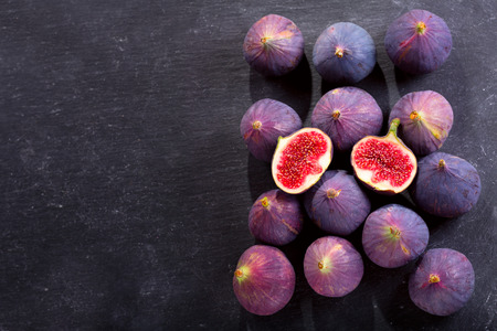 fresh ripe figs on dark background, top view