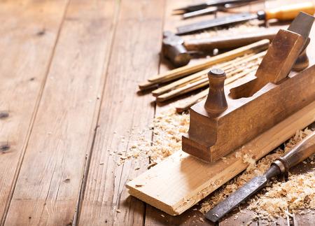 Herramientas antiguas: cepillo de madera, martillo, cincel en un taller de carpintería en la mesa de madera
