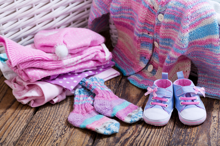 various baby clothes on wooden table Stock Photo