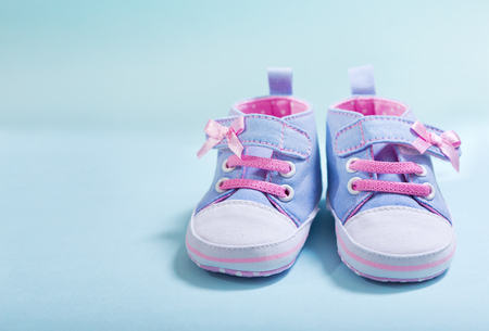 close up of baby sneakers on blue background