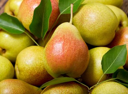 peras frescas con hojas como fondo, vista superior