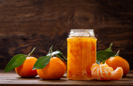 glass jar of tangerine jam with fresh fruits on wooden table