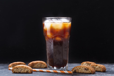 glass of iced coffee with cookies on dark table Stockfoto