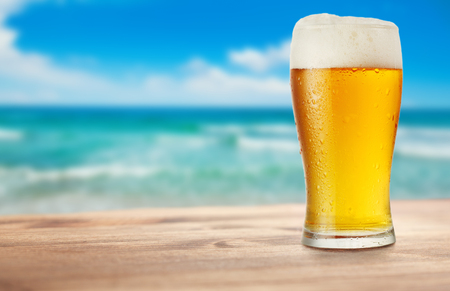 cold glass of beer on wooden table on background of sea