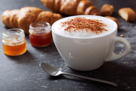 cup of cappuccino coffee with croissants on dark table