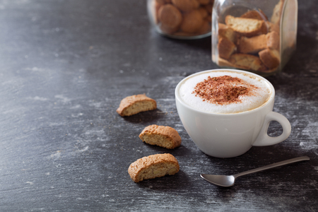 cup of cappuccino coffee with cookies on dark table Stockfoto