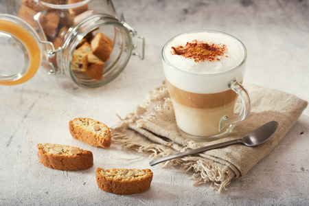glass of latte coffee with cookies