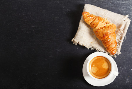 cup of coffee and croissants on dark table, top view