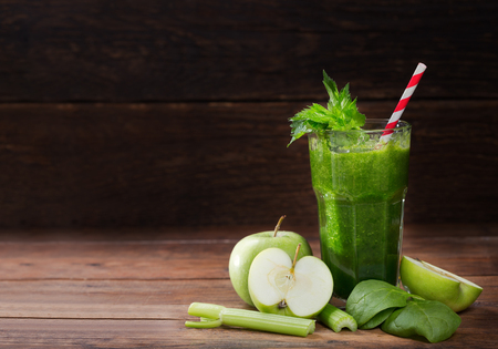 glass of green juice smoothie with spinach, apple and celery on wooden table