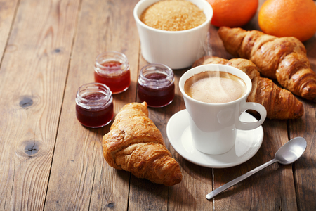 cup of coffee and croissants with fruit jam on wooden table Stockfoto
