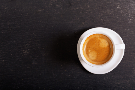 cup of coffee on dark table, top view