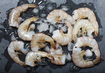 Fresh raw shrimps on dark table, top view Imagens