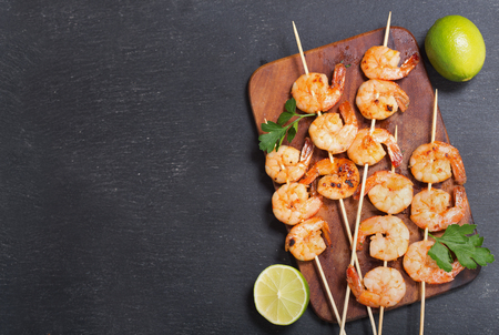 grilled shrimps with lime on a dark table, top view Stockfoto