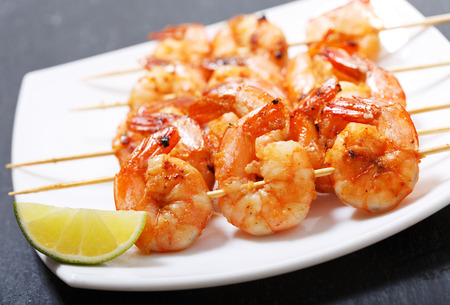 plate of grilled shrimps with lime on a dark table Stockfoto