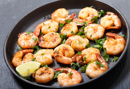 pan of grilled shrimps with lime on a dark table Stockfoto