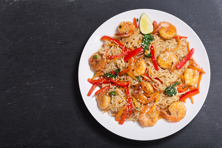 plate of Stir fried noodles with shrimps and vegetables on dark background, top view Stockfoto