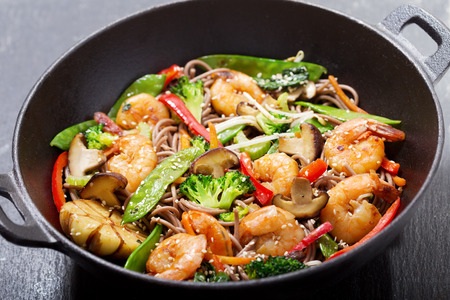 Stir fried noodles with shrimps and vegetables in a wok on dark background