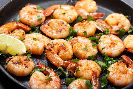 pan of grilled shrimps with lime on a dark table Фото со стока
