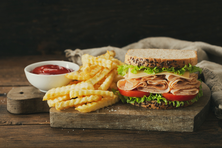sandwich with ham and french fries on wooden table Stockfoto