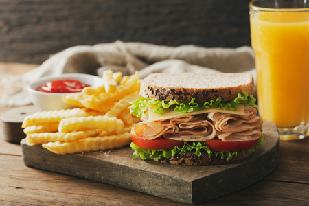 sandwich with ham, french fries and glass of orange juice on wooden table