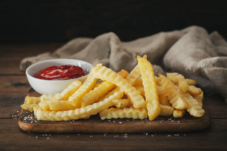 French fries with ketchup on wooden board