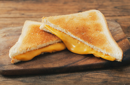 grilled cheese sandwiches on wooden board Stockfoto