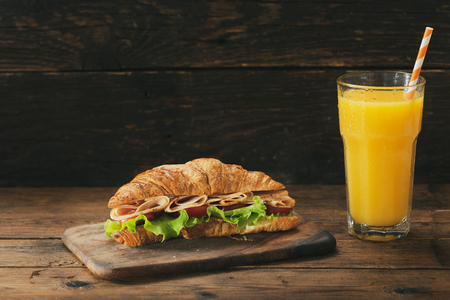 croissant sandwich with ham and glass of orange juice on wooden table