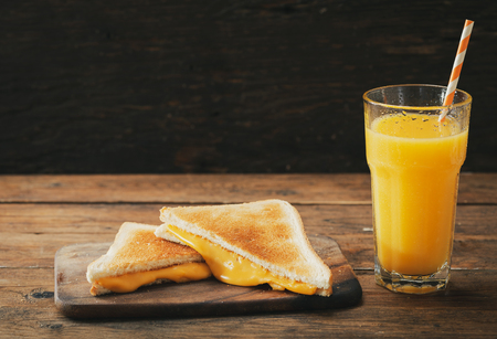grilled cheese sandwiches and glass of orange juice on wooden table