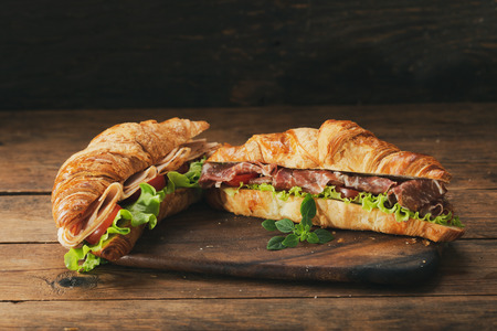 croissant sandwiches with ham and vegetables on wooden table