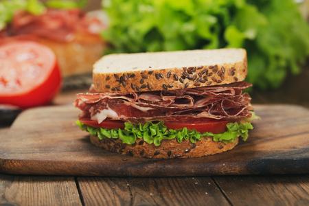 Sándwich de jamón y verduras en la mesa de madera